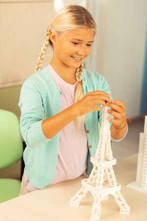 Enthusiastic pupil. Cheerful blond girl standing near her desk and building Eiffel tower miniature using construction set at school. Zdjęcie Seryjne