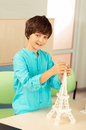 Imagining future profession. Happy boy standing at the schooldesk building a miniature of Eiffel tower using white construction set.