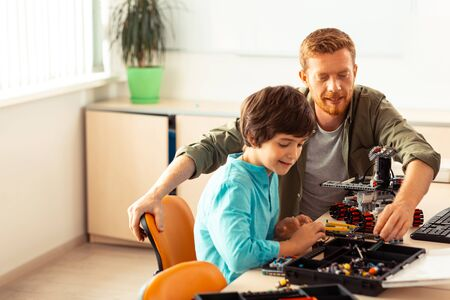 Asking for advice. Smiling schoolboy sitting with his teacher in the light classroom and making a robot of construction set with his help.