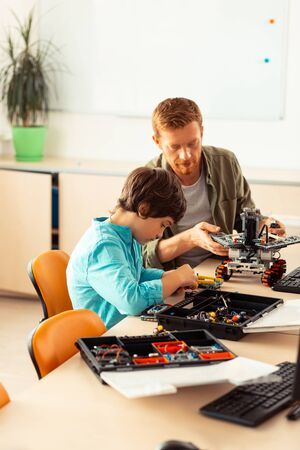 Lesson of constructing. Concentrated pupil sitting in the classroom and building robot out of construction set in front of his teacher.
