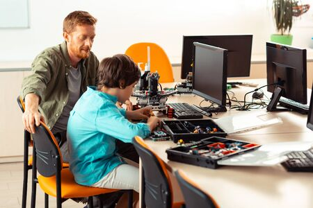 Process of creating. Supportive teacher sitting next to a pupil keeping an eye on him while he building a robot using construction set in computer lab.