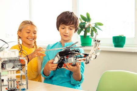 Good job. Smiling schoolgirl touching and looking at helicopter made with construction set by her classmate standing next to her.