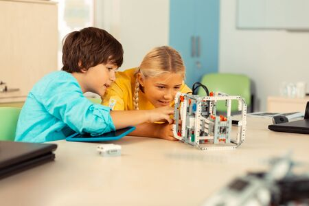 Self development. Enthusiastic schoolchildren sitting at the school desk with a tablet and looking closely at the model they building with construction set. Фото со стока