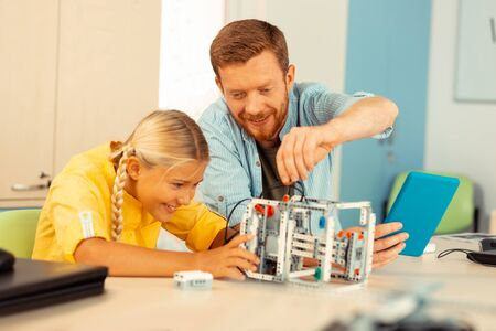 Learning science. Smiling teacher building a robot out of construction set and wires with one of his enthusiastic pupils.