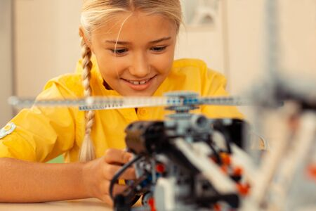 Playing with technics. Cheerful blond schoolgirl sitting at her desk and absorbedly playing with a helicopter model turning it on.