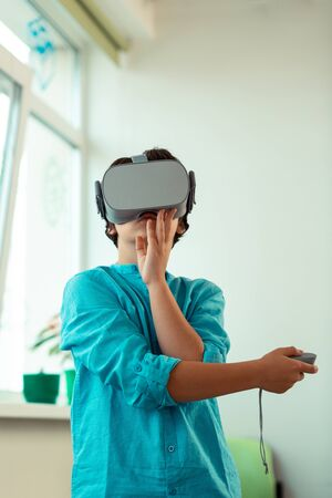 Feeling realistic. Impressed pupil playing virtual games wearing big VR glasses during his school lesson. Фото со стока