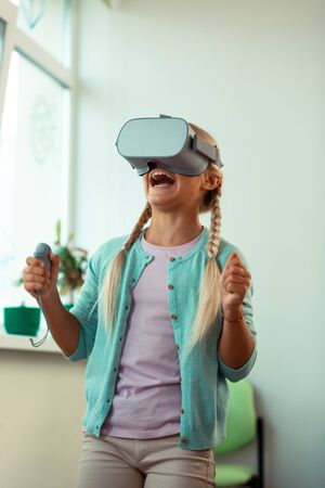 Feeling like a winner. Happy girl wearing VR glasses shouting with joy being excited winning virtual game.