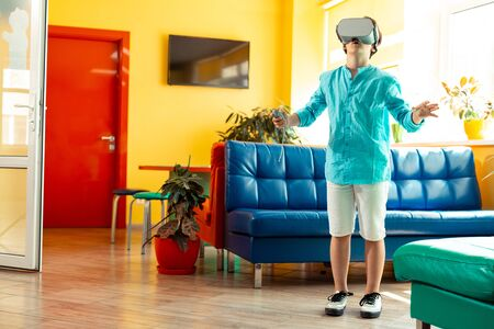 Impressive opportunities. Little boy wearing VR glasses standing in the hall of his school raising his hands being surprised with options of virtual reality.
