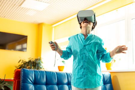 Child of new time. Smiling schoolboy wearing big VR glasses opening his mouth and raising hands being in raptures about the virtual reality. Фото со стока
