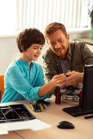 Showing the right way. Smiling science teacher helping his hard-working pupil with robot building sitting with him in computer lab.