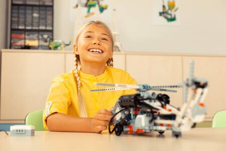 Loving science. Cheerful girl with a helicopter model in hands being happy attending her favorite school lesson. Фото со стока