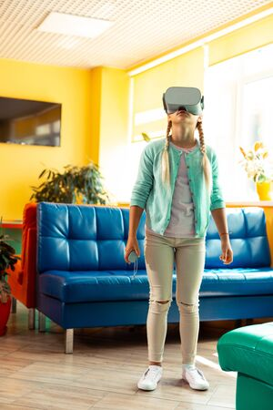 New world. Interested schoolgirl standing in the middle of school hall wearing VR glasses getting acquainted with virtual reality.
