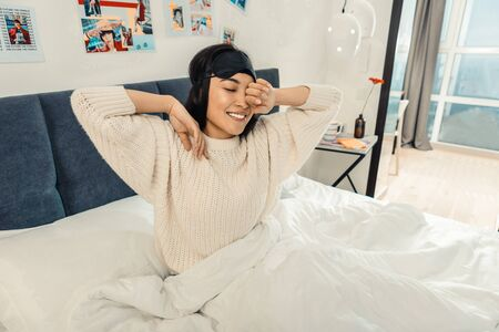 Sleepy young lady smiling and rubbing her eyes after waking up in her bedroom Stock Photo