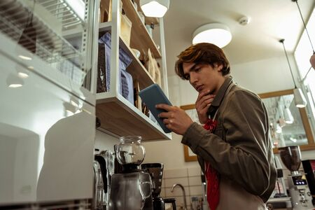 Handsome young man inventories packets of coffee at the coffee shop