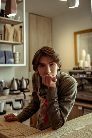 Portrait of an attractive young male leaning on bar counter looking straight into the camera