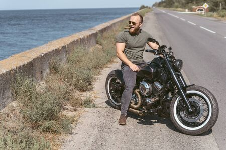 Attractive bearded man posing on motorcycle at the side of the road Stok Fotoğraf