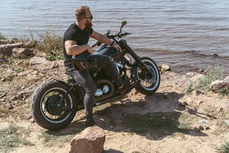 Handsome bearded guy posing on his motorcycle while looking at the ocean