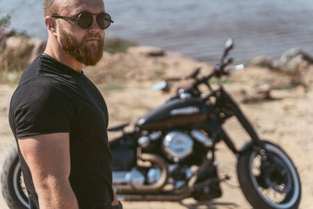 Handsome fit guy posing next to his motorbike