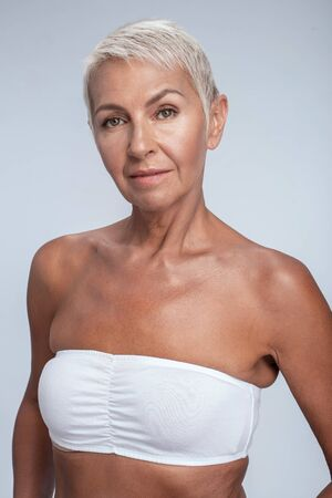 Beautiful middle aged woman posing in bra