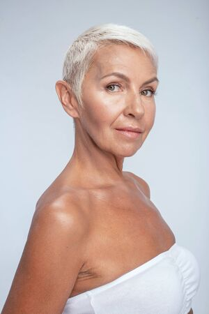 Beautiful woman in white bra standing with her side to the camera
