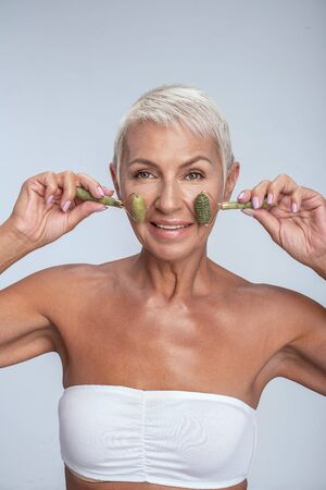 Pretty and fit female holding two jade rollers to her face