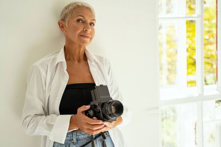 Delighted mature woman leaning on wall while creating new ideas for shooting