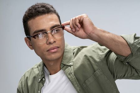 Good-looking young male fixing his glasses with one hand Фото со стока
