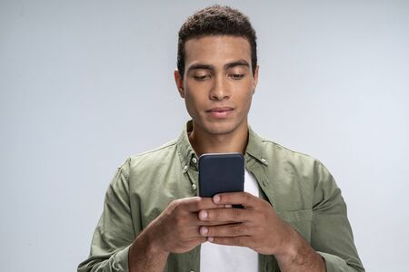 Good-looking male looking at the smartphone in his hands Фото со стока