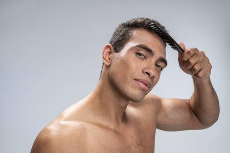 Good-looking young male brushing his short dark hair Фото со стока
