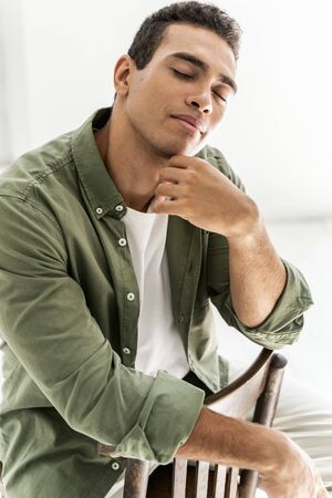Good-looking young male closing his eyes sitting on the chair