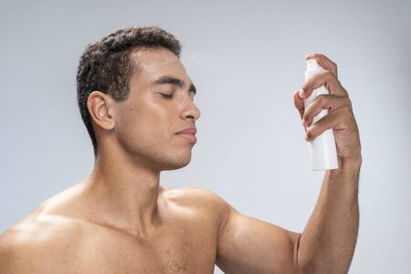 Good-looking man spraying his face with eyes closed