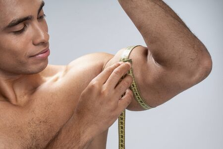 Good-looking young man taking measures of his biceps