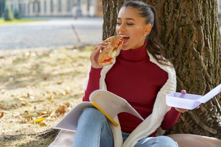 Good-looking young woman taking a bite of a big sandwich sitting under a tree