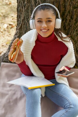 Cheerful young woman with a smartphone in hand listening to music and eating