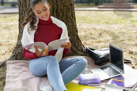 Pretty young woman sitting under a tree with her books and laptop