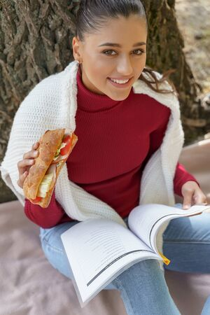 Cheerful young woman reading her book and eating sitting outside