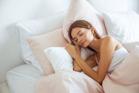 Feeling calmness. Sleepy female keeping eyes closed while dreaming about future vacation