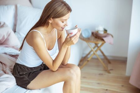 Life enjoyment. Pleased brunette girl keeping eyes closed while having morning meditation 版權商用圖片