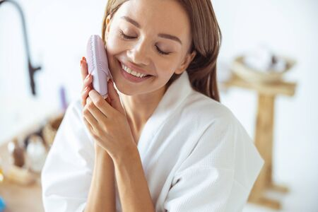 Close up of pleased girl that keeping eyes closed while doing face massage