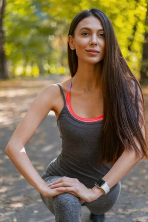 Good-looking young female putting her hands on a knee during stretching Reklamní fotografie