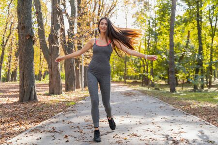 Good-looking young happy lady going to run in the autumn park Reklamní fotografie
