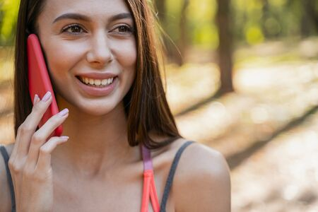 Close up picture of a good-looking young lady talking on her smartphone Reklamní fotografie