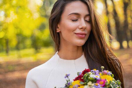 Belle jeune femme avec des fleurs dans les mains fermant les yeux Banque d'images