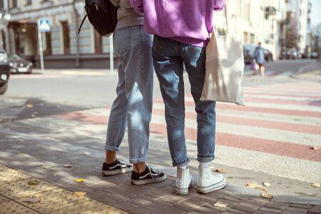 Street style. Young women standing near crosswalk, looking in one direction