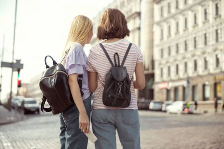 Choosing direction. Pretty girls standing on crosswalk and looking in one direction