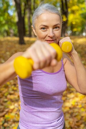 Mature female working on her biceps using dumbbells