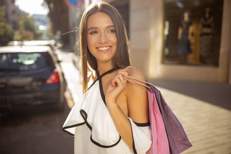 Beautiful young woman holding her shopping bags on the shoulder before crossing the road