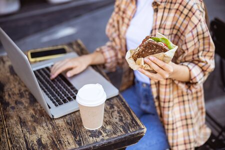 Close-up picture of a sandwich in hand of young female sitting at the laptop