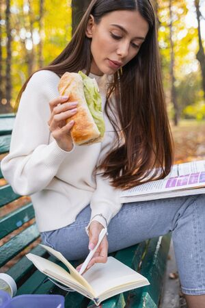 Attentive young woman eating sandwich for dinner while sitting in the park Imagens