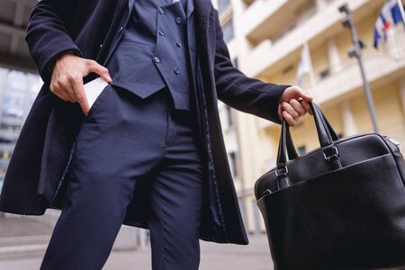 Close up of serious businessman that carrying his bag while taking telephone for making call Zdjęcie Seryjne